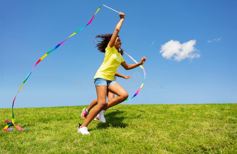 Kids run holding ribbon in park, profile view. Kids run with ribbon on the clean grass and sky background profile view stock images