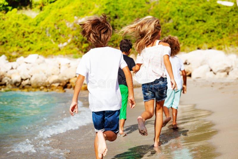 Kids running away along sandy beach in summer stock photos