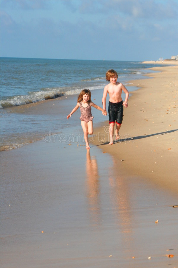 Kids running on the beach stock image