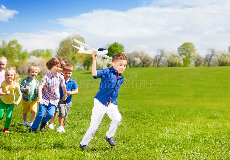 Kids running and boy holding white airplane toy. Kids running together and boy holding big white airplane toy in the field during summer sunny day stock images