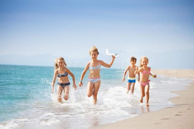 Kids running on coast and playing with toy plane stock photography