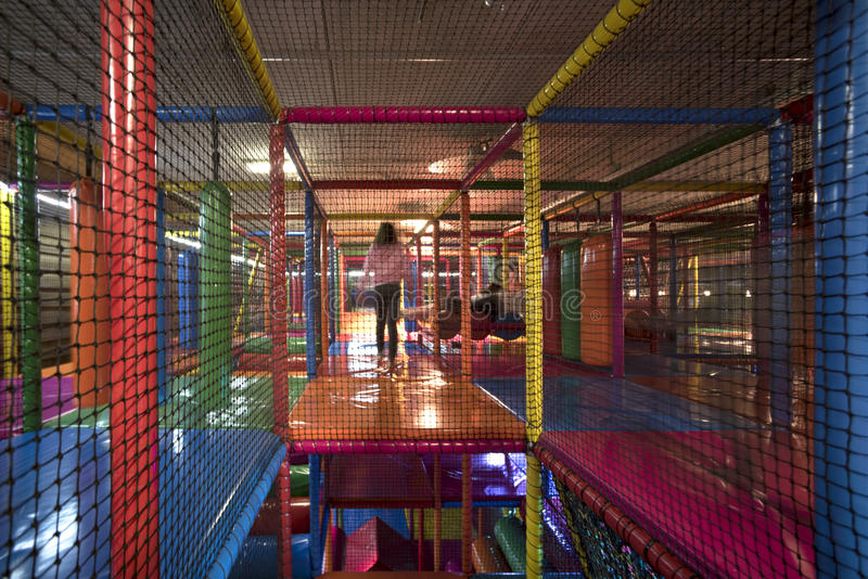 Kids running inside a Colorful indoor playground. Blurry kids running inside colorful 3D Net Maze, indoor playground for kids with bumpers, punching cylinder stock images