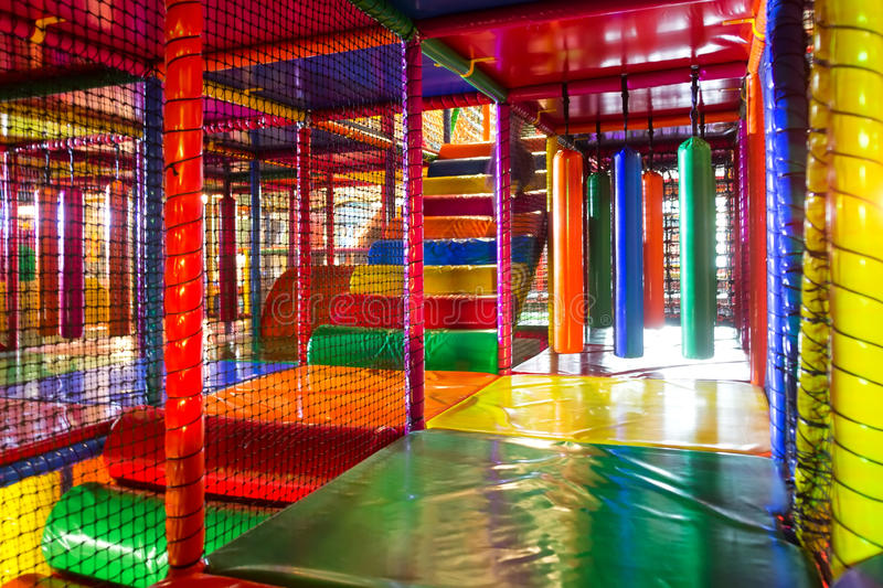 Kids running inside a Colorful indoor playground. Colorful 3D Net Maze indoor playground for kids with bumpers, punching cylinder, slide, bridge, balls stock photo