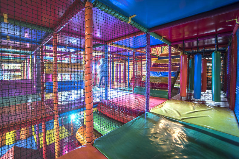 Kids running inside a Colorful indoor playground. Kids running inside colorful 3D Net Maze, indoor playground for kids with bumpers, punching cylinder, slide stock photos