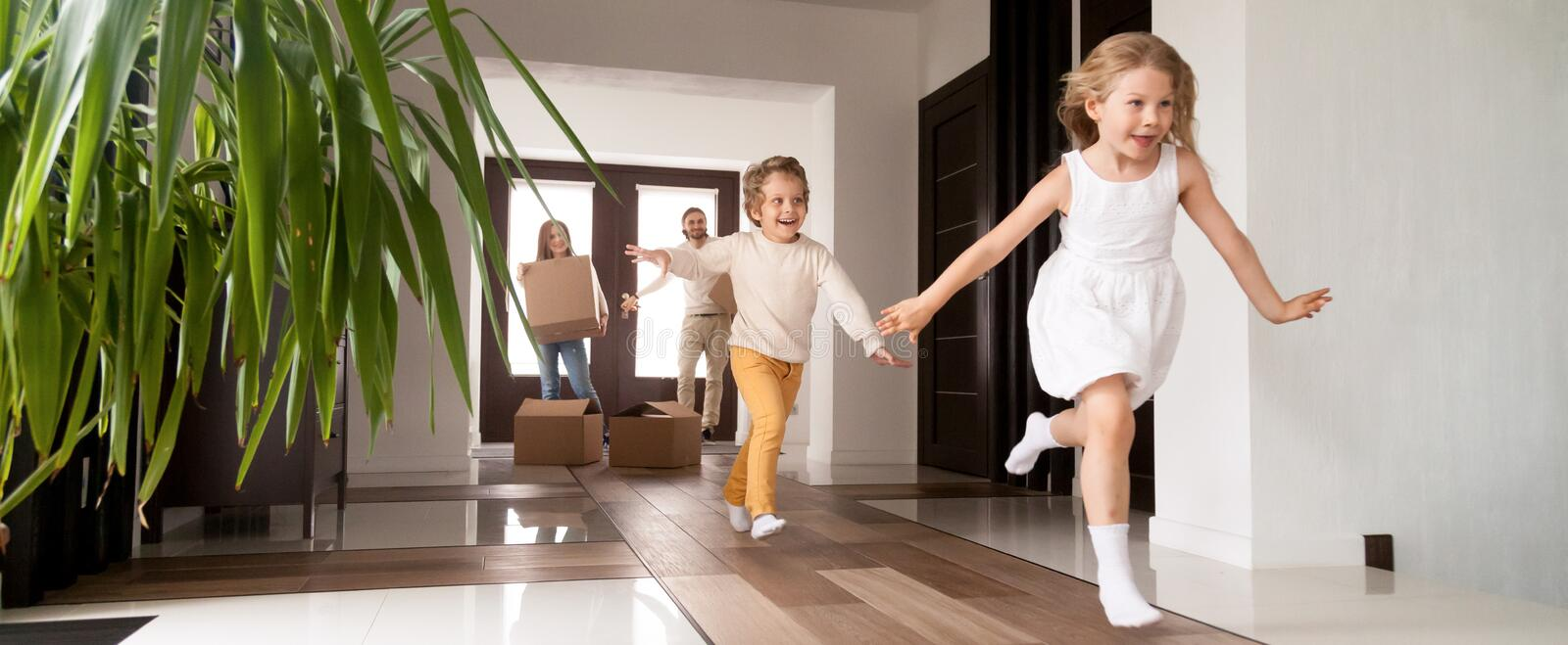 Kids running into new house parents with boxes on background royalty free stock image