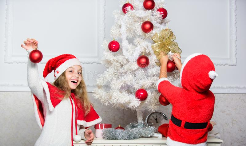 Kids in santa hats decorating christmas tree. Family tradition concept. Children decorating christmas tree together. Boy stock image