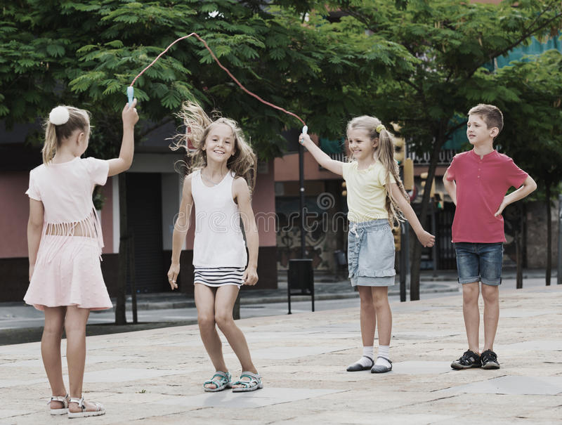 Kids in school age playing together with jumping rope. Happy cheerful kids in school age playing together with jumping rope outdoors stock image