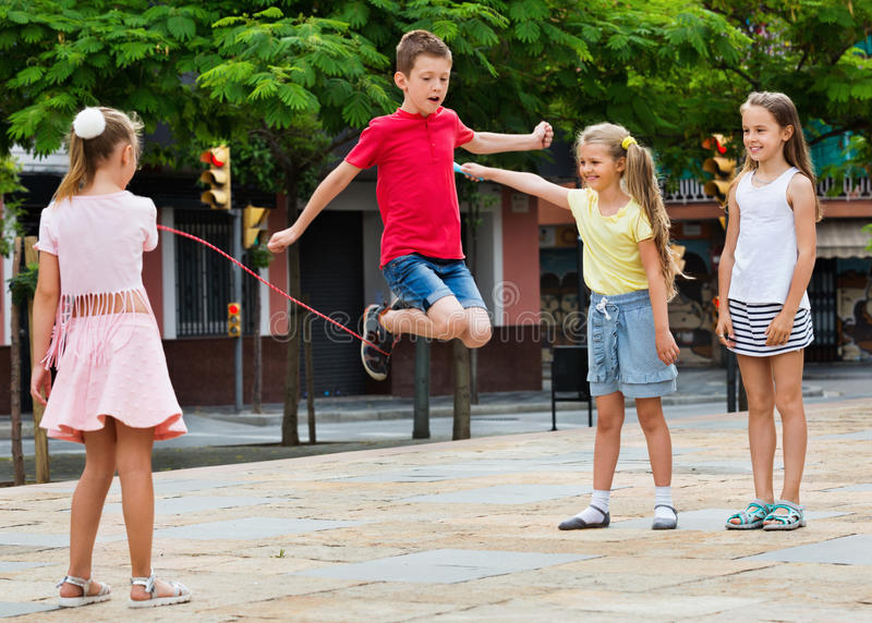 Kids in school age playing together with jumping rope. Smiling cheerful kids in school age playing together with jumping rope outdoors stock images