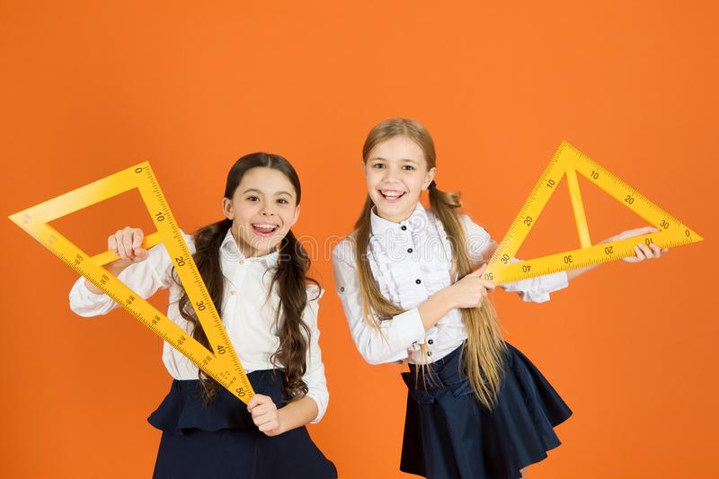 Kids school uniform on orange background. Pupil cute girls with big rulers. Geometry school subject. Drawing with ruler stock photography