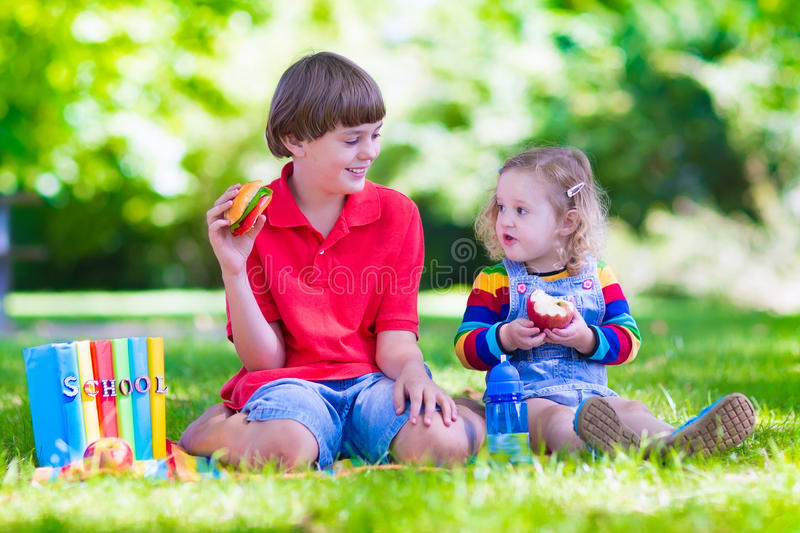 Kids in school yard. Children in school yard. Happy laughing teenager student boy and preschool girl in the school garden reading books and having apple for royalty free stock photo
