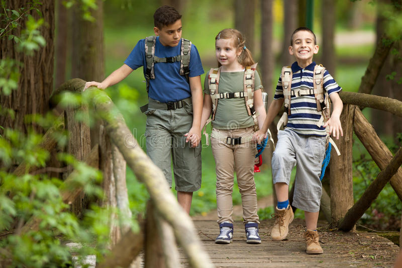 Kids scouts traveler with backpack hiking on bridge. Boys and girl go hiking with backpacks on forest road stock image
