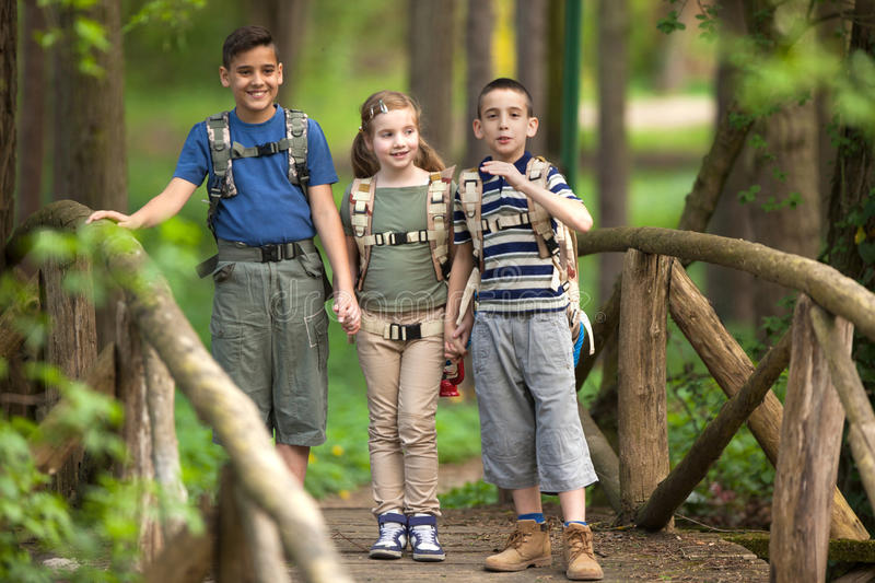 Kids scouts traveler with backpack hiking on bridge. Boys and girl go hiking with backpacks on forest road stock images