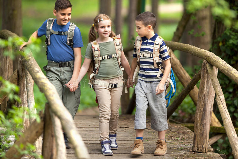 Kids scouts traveler with backpack hiking bridge in forest. Boys and girl go hiking with backpacks on forest road stock image