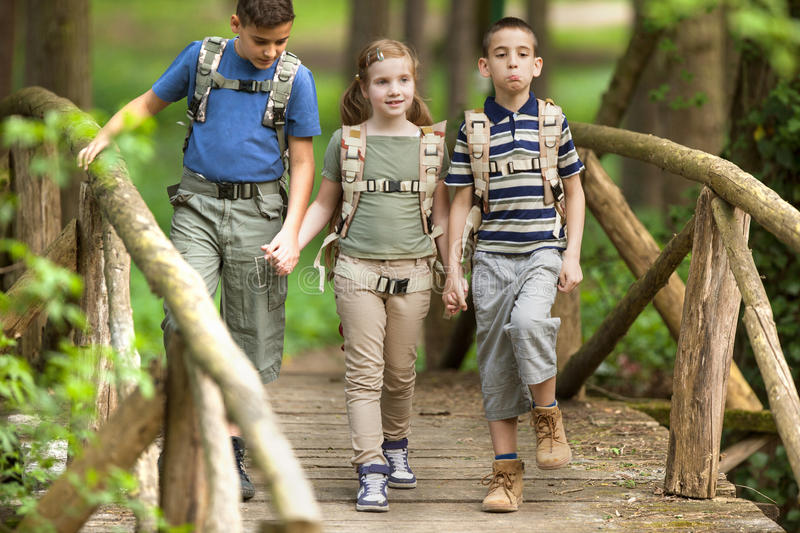 Kids scouts traveler with backpack hiking bridge in forest. Boys and girl go hiking with backpacks on forest road royalty free stock photography