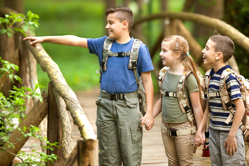 Kids scouts traveler with backpack hiking bridge in forest. Boys and girl go hiking with backpacks on forest road stock images