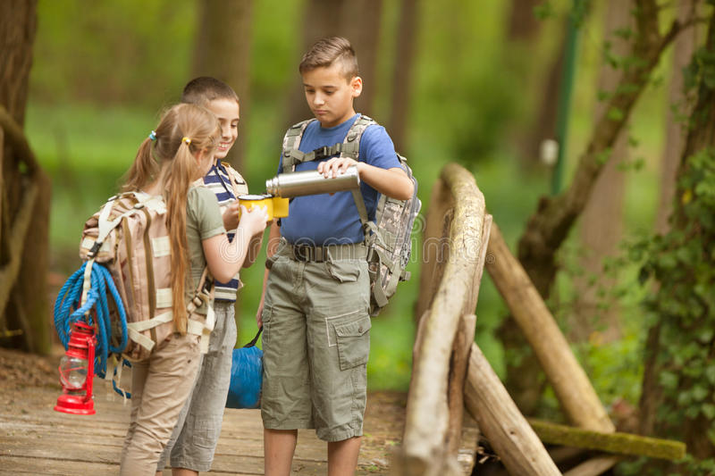 Kids scouts traveler with backpack hiking bridge in forest. Boys and girl go hiking with backpacks on forest road stock photo