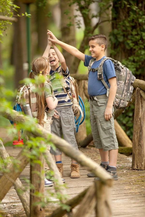 Kids scouts traveler with backpack hiking bridge in forest. Boys and girl go hiking with backpacks on forest road royalty free stock images
