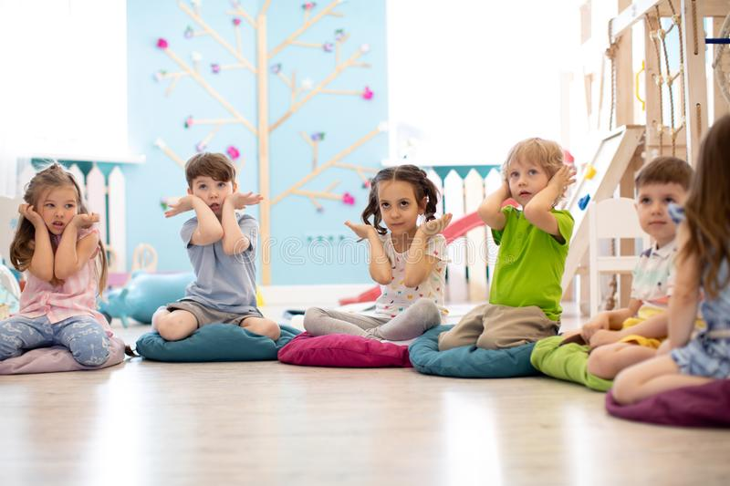 Kids seating on floor and show gestures making task stock photo