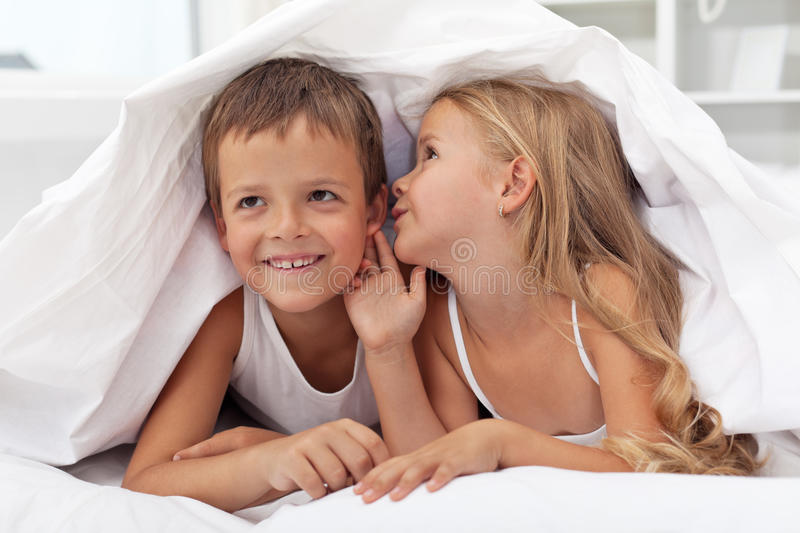 Kids sharing their secrets under the quilt royalty free stock images