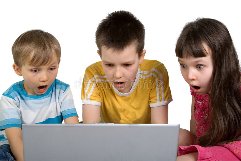Kids Shocked by Something on Computer. Three kids are shocked by seeing something unexpected while playing on a laptop computer royalty free stock image
