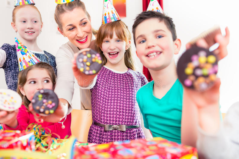 Kids showing muffin cakes at birthday party. Kids showing muffin cakes into the camera at birthday party, larger group of children and mother royalty free stock image