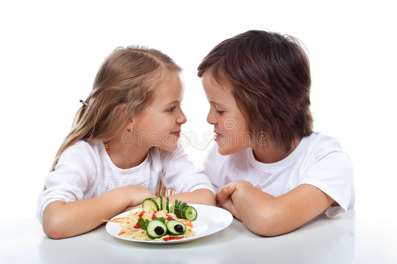 Kids sipping on the same string of pasta stock photo