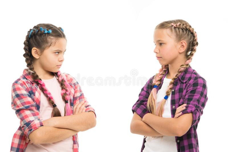 Kids sisters looks strictly. Girls folded arms on chest looks serious white background. Stubborn temper. Stubborn. Concept. Stubborn kids. Disagreement and royalty free stock images
