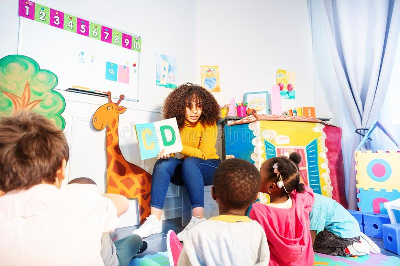 Kids sit around teacher and learn alphabet stock photography