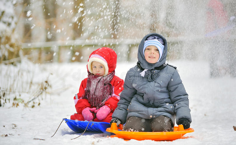 Kids sit on sled. In winter time stock image