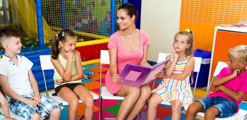 Kids sitting around teacher reading book stock photo