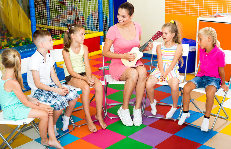 Kids sitting around teacher with small guitar stock photography