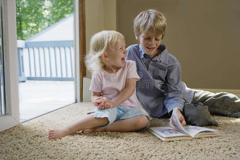 Kids Sitting On Carpet With Book stock photography