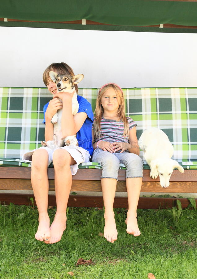 Kids sitting on a garden swing with dogs. Little boy and girl - kids sitting on a wooden garden swing with dogs stock photography