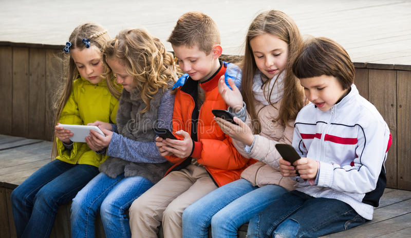 Kids sitting with mobile devices stock image