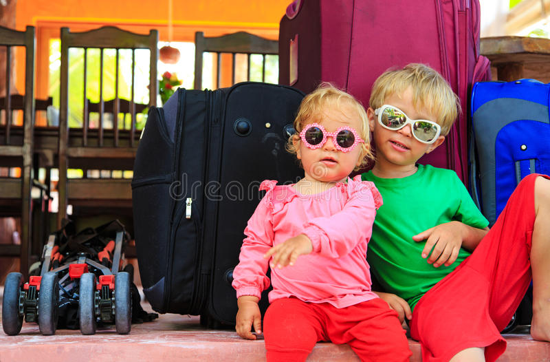 Kids sitting on suitcases ready to travel stock images