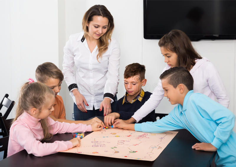 Kids sitting at table with board game and dice at school royalty free stock image