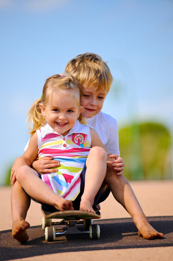 Kids on skateboard. Two young children sitting and playing with skateboard stock photo