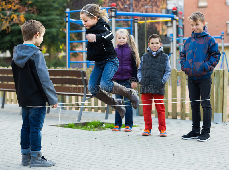 Kids skipping on chinese jumping elastic rope in yard. Happy spanish kids skipping on chinese jumping elastic rope in yard royalty free stock photography