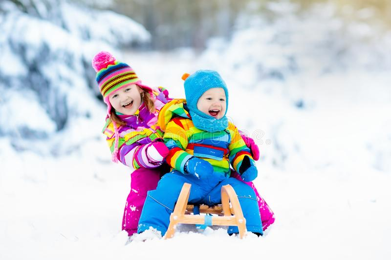 Kids on sleigh ride. Children sledding. Winter snow fun. Little girl and boy enjoy a sleigh ride. Child sledding. Toddler kid riding a sledge. Children play royalty free stock photography