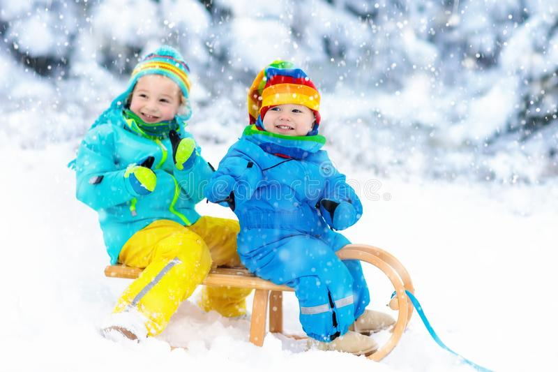 Kids on sleigh ride. Children sledding. Winter snow fun. Little girl and boy enjoy a sleigh ride. Child sledding. Toddler kid riding a sledge. Children play royalty free stock photos