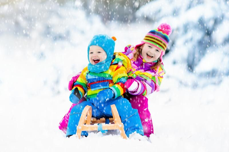 Kids on sleigh ride. Children sledding. Winter snow fun. Little girl and boy enjoy a sleigh ride. Child sledding. Toddler kid riding a sledge. Children play stock photos