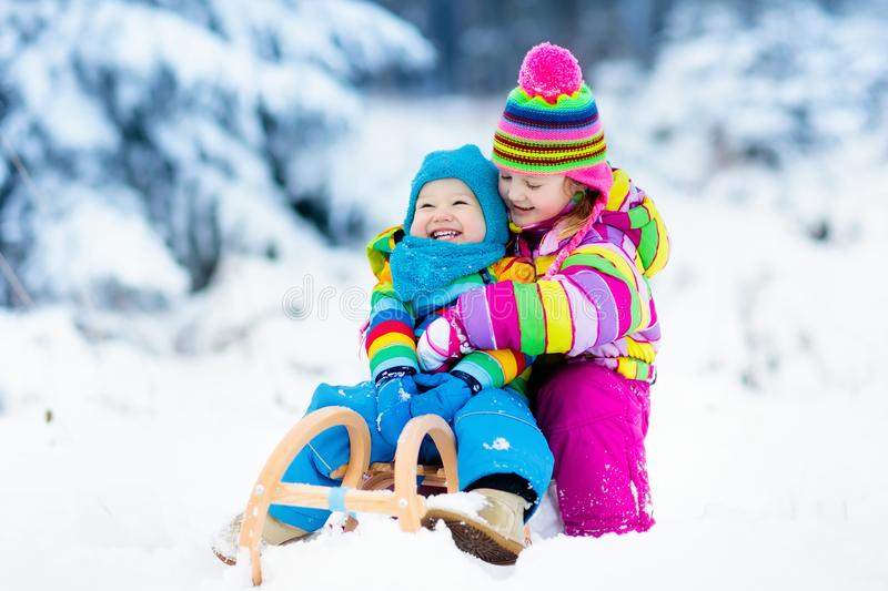 Kids on sleigh ride. Children sledding. Winter snow fun. Little girl and boy enjoy a sleigh ride. Child sledding. Toddler kid riding a sledge. Children play stock photography