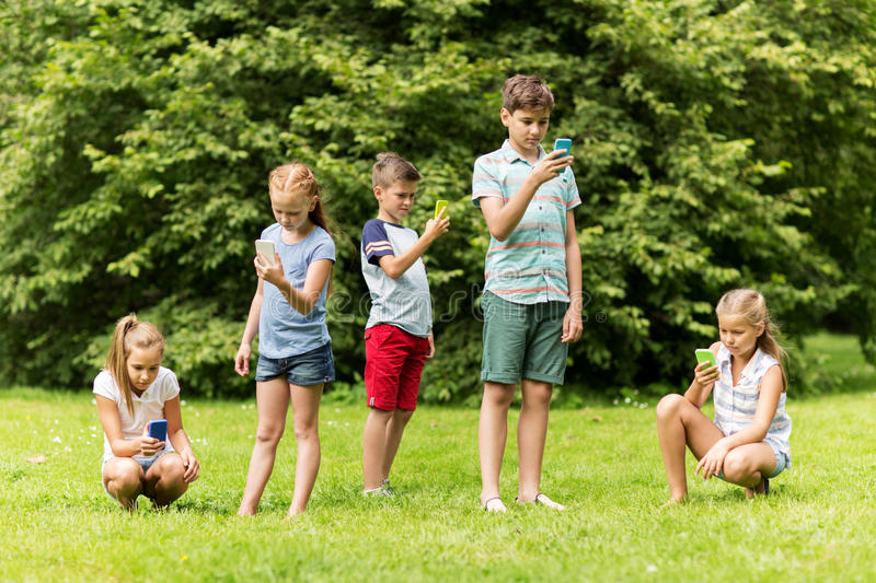 Kids with smartphones playing game in summer park royalty free stock photography