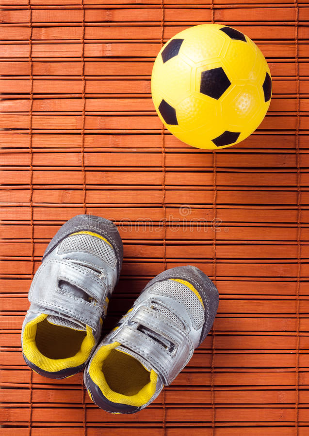 Kids sneakers and soccer ball on a hardwood floor. The view from the top stock photos