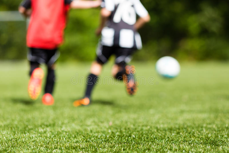 Kids soccer blur. Picture of kids soccer training match with shallow depth of field. Focus on foreground royalty free stock photo