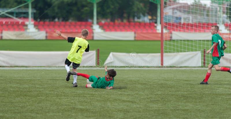 Kids' soccer. Boys kicking football on the sports field royalty free stock photo