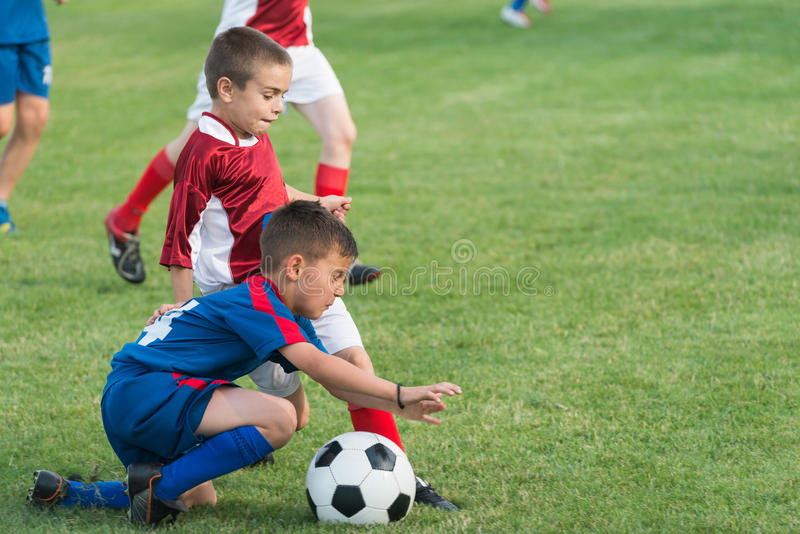 Kids' soccer. Boys kicking football on the sports field stock images