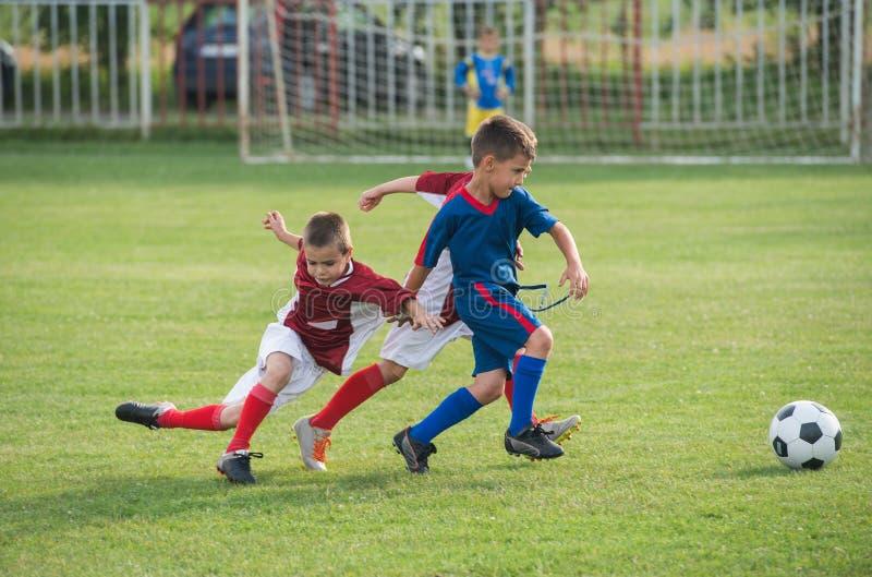 Kids' soccer. Boys kicking football on the sports field royalty free stock photos