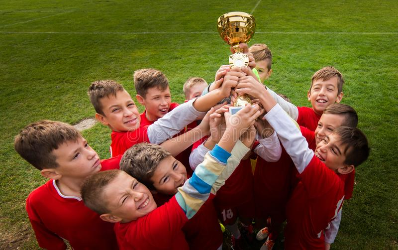 Kids soccer football - children players celebrating with a trop. Kids soccer football - young children players celebrating with a trophy after match on soccer stock photography