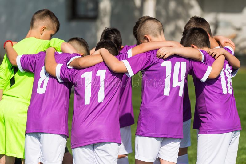 Kids soccer football - children players celebrating after victo. Kids soccer football - young children players celebrating in hug after victory royalty free stock image